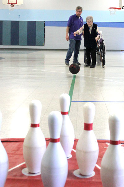 Steve Sarrazin helps Catherine Tarnowski as she aims for a strike during Langford's Weekly Senior Group. (Park Bugle photo by Kristal Leebrick)