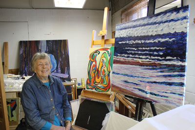 Bettye Olson, 91, will open her studio during the Do the Dow art crawl. Olson is shown here with a painting from her early years (the 1940s) to one she painted in 2014 (right). (Photo by Kristal Leebrick)