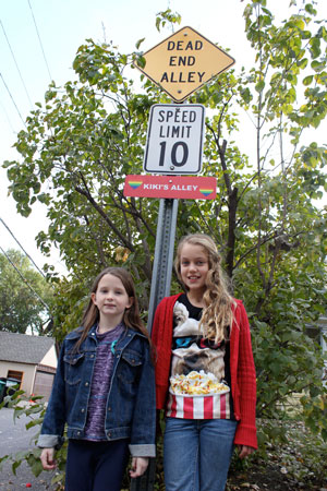 Maggie Fuller (left) and Maddie Thompson and the sign they created to honor their neighbor, Kiki Gore. (Photo by Kristal Leebrick)