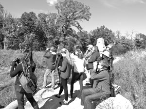 Volunteers and Great River School students birding during an educational workshop in the Como Woodland Outdoor Classroom