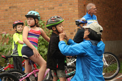 John Mark Lucas  helps fit a bike helmet onto Tianze Wen, a first-grader. Also in the photo are Greta Seppanen, fourth grade, and Elliot Lindsley, first grade.
