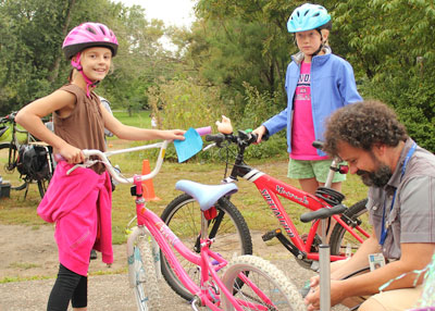 Bike rodeo coordinator Dan Clark (right) pumps air into the back tire of the bike belonging to fourth-grader Alice Wagner-Hemstad (left). The other student in the photo is fellow fourth-grader Siri Pattison.