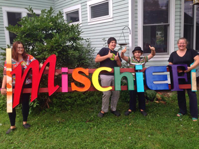 Abby, Riley and Duncan Adelsheim-Marshall and Millie Adelsheim hold the Mischief sign.