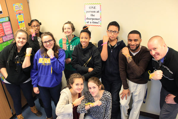 "Some members of the Murray Dare 2B Real group show the ribbons they wore on their wrists on Feb. 9 to remind them to ""check themselves"" when they stereotype. Shown here, back row from left: teacher Kate Hunziker, Avani Holcomb, Stella LaCroix-Dulluhn, Amira Boler, Sadie Murphy, Hever Pliego, teacher Lorenzo Farley and assistant principal Jamin McKenzie. Kneeling are Fiona Juarez-Sweeney and Amelia Moseman. Photos by Kristal Leebrick"