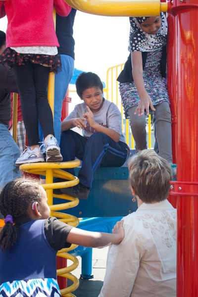 A student converses with executive director Susan Lane-Outlaw on the playground. Photo by Lori Hamilton.