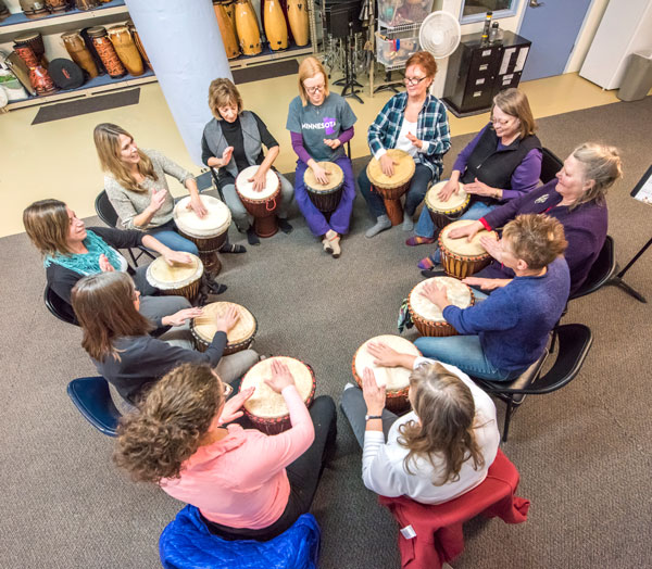 Bettie Seitzer (far right) leads a Tuesday night drumming circle in the basement of the Dow Building on University Avenue. Photo by Mike Krivit